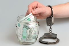 Hand in handcuffs taking money from glass jar on gray Royalty Free Stock Photography