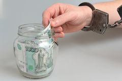 Hand in handcuffs taking money from glass jar on gray Royalty Free Stock Images