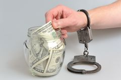 Hand in handcuffs taking money from glass jar on gray Stock Image