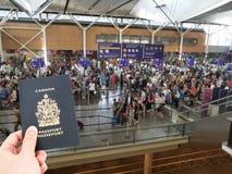Hand handing Canadian passport at airport customs royalty free stock photo