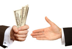 Hand handing over money to another hand Stock Image