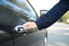 Hand on handle. Close-up of female hand opening a car door. Hand on handle. Close-up of female in formal wear opening a car door Stock Photo