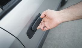 Hand on handle. Man hand opening a car door stock photo