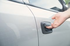 Hand on handle. Man hand opening a car door stock photography
