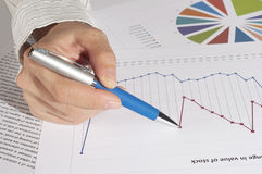 Hand with the handle specifies charts of growth Stock Image