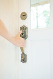 Hand on a handle wooden door to open Stock Image