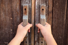 Hand on a handle wooden door. To open or close it Stock Image