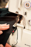 Hand handles the black cloth on the serger. Stock Images