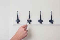 Hand hangende sleutel op haak Stock Fotografie