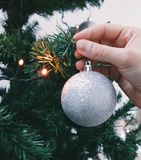Hand hanging Christmas ornament royalty free stock image