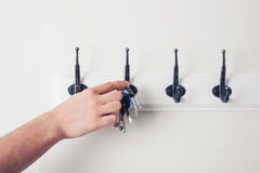 Hand hanging key on hook Stock Photos