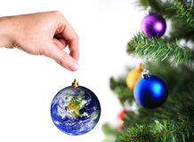 Hand hanging up earth decoration on christmas tree Stock Images