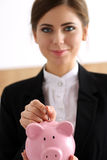 Hand of happy smiling businesswoman putting pin money into pink Royalty Free Stock Photos