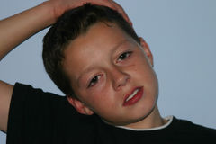 Hand on head. Teenage boy close up with right hand resting on his head royalty free stock photo
