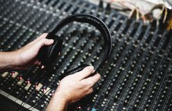 Hand with headphone on sound mixer Royalty Free Stock Image
