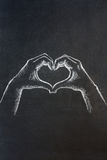 Hand heart. Chalk illustration of human male's hands in the shape of a heart on a blackboad Royalty Free Stock Photos