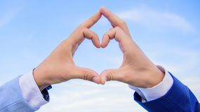 Hand heart gesture forms shape using fingers. Hands put together in heart shape blue sky background. Love symbol concept. Male hands in heart shape gesture royalty free stock images