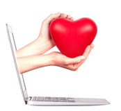 Hand with a heart - gift and laptop. Hand with a heart - gift come out from a screen of a laptop computer isolated on white background Royalty Free Stock Images