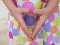 Hand heart. Little girl's sandy hands making a heart on a polka dot dress background Stock Images