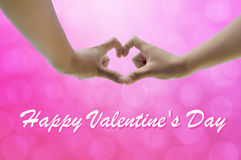 Hand on heart-shaped pink background on Valentine's Day. Stock Photography
