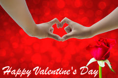 Hand on heart-shaped red background and rose on Valentine's Day. Royalty Free Stock Photo
