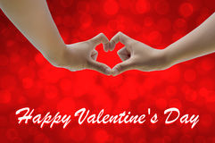Hand on heart-shaped red background on Valentine's Day. Stock Photo