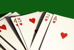 A hand of hearts only playing cards on dark green background. stock photos
