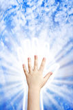 Hand of heaven. Child's hand in the hand of heaven Stock Photography
