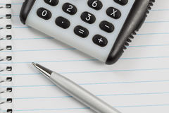Hand Held Calculator and Pen on Notepad Paper Royalty Free Stock Images