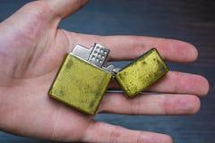 Hand-held golden folding lighter stock photo