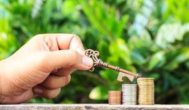 Hand held keys and coins. Business success concept Stock Image