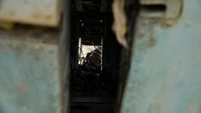 View through a narrow space. A hand held, long shot of the view seen through a narrow space between metal scraps stock video footage