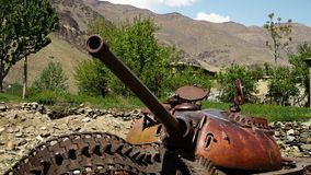 The front view of a tank. A hand held, medium shot of the front view of a tank and some green trees in the background stock video footage