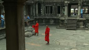Monks dressed in red talking to people. A hand held, medium shot of two monks dressed in red robes talking to people who are visiting the temple stock footage