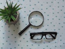 Hand-Held Reading Magnifier, Magnifying Glass, a Pair of Glasses with Black Frame and Green Flowers on Patterned Background. . Hand-Held Reading Magnifier royalty free stock image