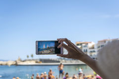 Hand held smartphone taking a picture in the beach of l`Escala. Costa Brava, Girona province, Spain. Stock Photo