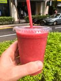 Hand held strawberry smoothie. Royalty Free Stock Photos