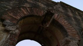 The arcade of a door in the wall. A hand held, tilting, panning, close up shot of the arcade made of red bricks in a wall of a fortress stock footage