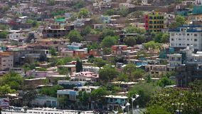 Colourful houses on a hill. A hand held, wide shot of a road situated at the bottom of a hill filled with colourful houses stock video footage