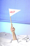 Hand with help flag sticking out of papers Royalty Free Stock Photos
