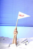 Hand with help flag sticking out of papers Stock Photography