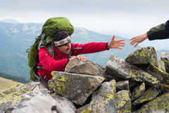 Hand helping hiker to climb the mountain Stock Photos