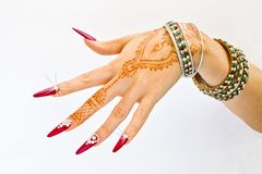 Nails decorated with brilliant and hand with henna tattoos. Hand with henna tattoo, nails decorated with brilliants and bracelets with precious stones royalty free stock photography