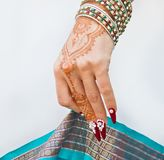 Nails decorated with brilliant and hand with henna tattoos. Hand with henna tattoo, nails decorated with brilliants and bracelets with precious stones royalty free stock images