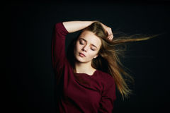 The hand in her hair. Beautiful young girl dancing. Hair flying. Shooting in Studio on dark background Royalty Free Stock Photos