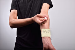Hand with heroin syringe with post it Stock Photos