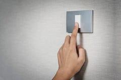 Hand het aanzetten of weg op grijze lichte schakelaar met textur stock afbeelding
