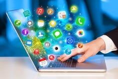 Hand het drukken moderne laptop met mobiele app pictogrammen en symbolen Stock Foto
