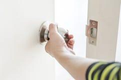 Hand het openen deurknop, witte deur Stock Fotografie