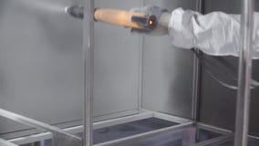 Hand het schilderen van een metaaloppervlakte door spuitpistool klem De mens in een beschermend kostuum schildert de fabriek stock footage